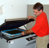 Mier Products can silk-screen your logo or graphic to your metal enclosure: Step 3, exposure unit burns image on screen.